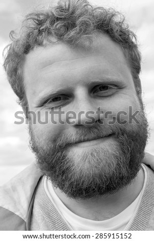 Young red bearded hipster looking into camera - stock photo