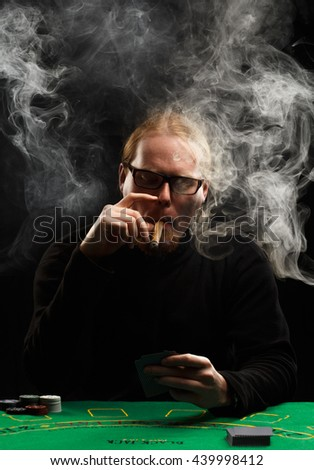 Young red-haired bearded man in glasses and black pullover with a cigar and cards sitting at poker table covered with green cloth in a puff of smoke. - stock photo