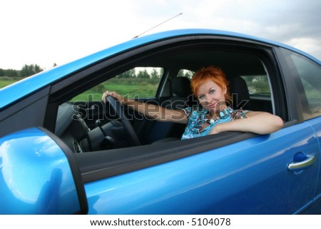 Young red-haired woman is siting in a car. Woman is happy - stock photo