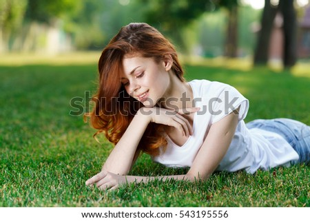 Young red-haired woman lying on the grass in the park