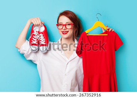 Young redhead designer with dress and gumshoes on blue background - stock photo