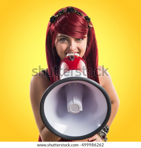 Young redhead girl shouting by megaphone over colorful backgound