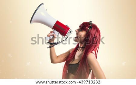 Young redhead girl shouting by megaphone over ocher background