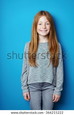 Young redhead girl with an engaging smile standing in front of turquoise blue background with copy space - stock photo