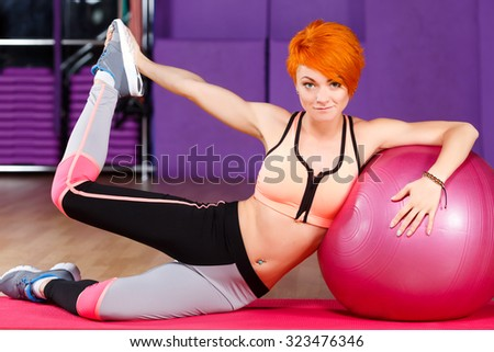 Young redhead girl, with short haircut, wearing in top and leggings, does exercises with pink fitball on the yoga mat, in the gym, full body