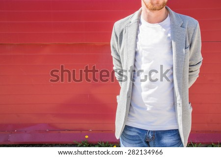 Young redhead muscular sexy man with beard wearing jeans, white T-shirt and grey cotton jacket standing near a red wall with hands behind a his back - stock photo