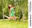 Young redhead woman jumping in the park with flowers - stock photo
