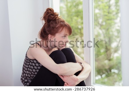 Young redhead woman sitting daydreaming on a windowsill staring out at the green leaves on the tree as she hugs her knees - stock photo