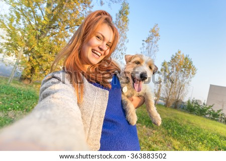 Young redhead woman taking selfie outdoors with cute dog - Concept of friendship and love with people and animals together - Sunny winter afternoon with warm color tones - Tilted horizon composition - stock photo