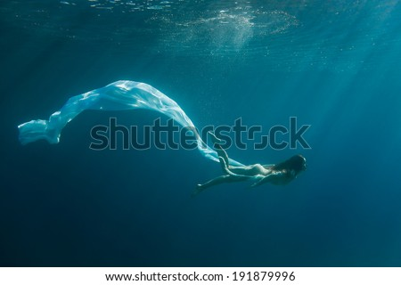 Young redhead woman underwater - stock photo