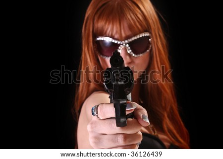 Young redhead woman with gun on black background - stock photo