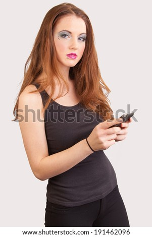young redheaded female on her cell phone white background  - stock photo