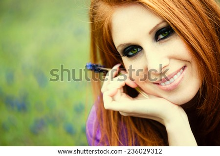 Young redheaded girl resting in spring flower field - stock photo