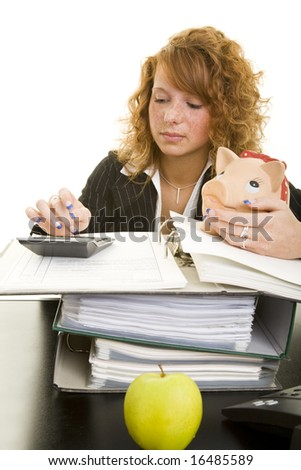 Young redheaded woman working at her desk - stock photo