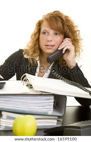 Young redheaded woman working at her desk
