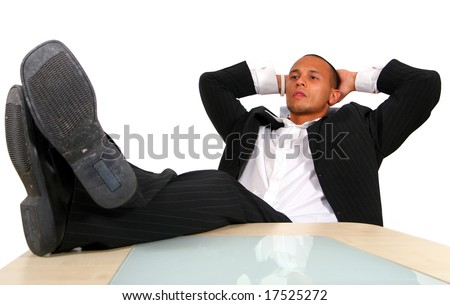 Young Relaxed Businessman A young satisfied businessman sitting by desk at office feet on table thinking. Isolated over white.