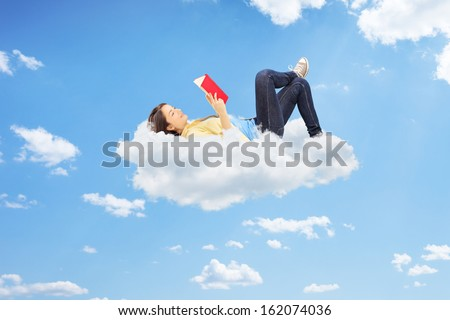 Young relaxed female reading a novel and lying on clouds - stock photo