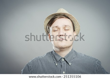 Young relaxed man in hat closed his eyes and dreams - stock photo