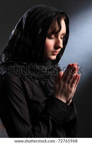 Young religious woman wearing black hijab headscarf, eyes closed and hands together in prayer. - stock photo