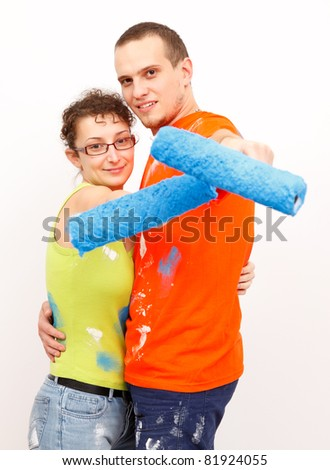Young renovating couple with paint rollers are showing to us, white background