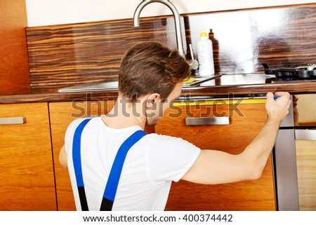 Young repair man measuring kitchen cabinet - stock photo