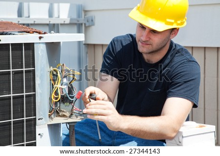 Young repairman fixing an industrial air conditioning compressor. - stock photo