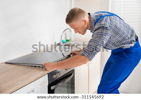 Young Repairman Installing Induction Cooker In Kitchen - stock photo