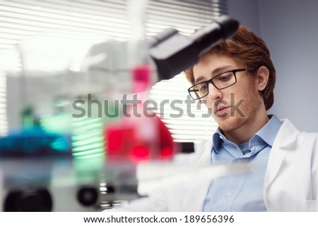 Young researcher at work with laboratory glassware on foreground. - stock photo