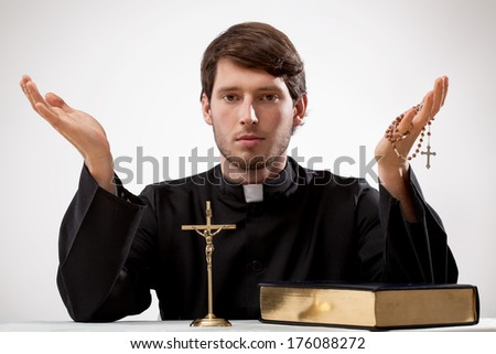 Young reverend with crucifix, rosary and the Bible - stock photo