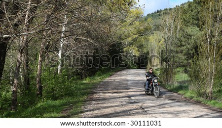 Young rider driving his cruiser-type motorcycle on the forest road. - stock photo