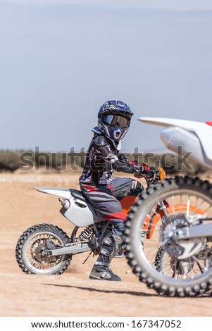 young rider on a motorcycle through the desert area, summer day - stock photo