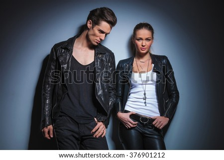 young rocker looking down with hand in pocket while his girlfriend pose in her leather jacket with hands on waist in studio background - stock photo