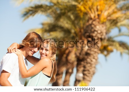 Young romantic beautiful couple enjoying on a walkside with threes - stock photo