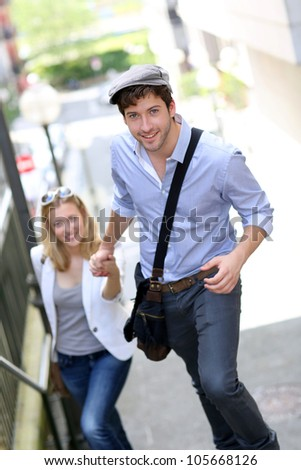 Young romantic couple climbing stairs in town - stock photo