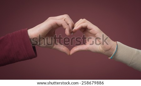 Young romantic couple composing an heart shape with hands - stock photo