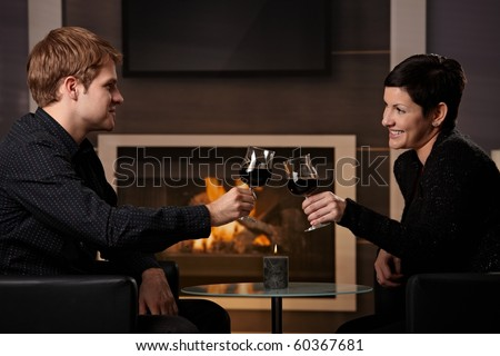 Young romantic couple dating, sitting in front of fireplace at home, drinking red wine. - stock photo