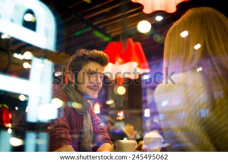 Young romantic couple eating at city restaurant by evening - stock photo