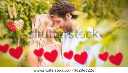 Young romantic couple embracing each other against hearts hanging on a line - stock photo