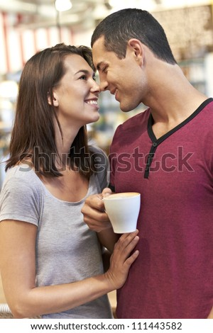 Young romantic couple enjoying coffee while staring into each others eyes - stock photo