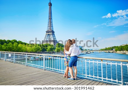 Young romantic couple having a date and looking at the Eiffel tower on a bridge over the Seine in Paris, France - stock photo