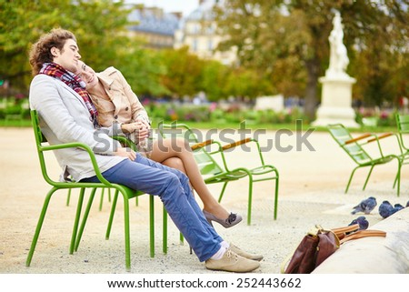 Young romantic couple having a date in the Tuileries garden of Paris - stock photo