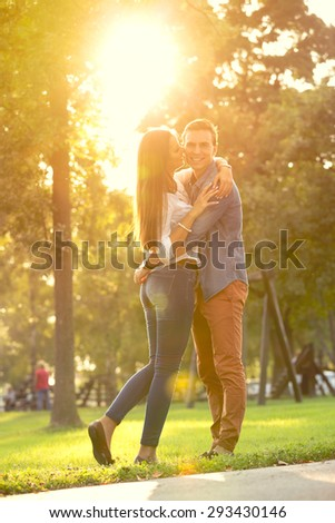 Young romantic couple hugging in sunny park full length  - stock photo
