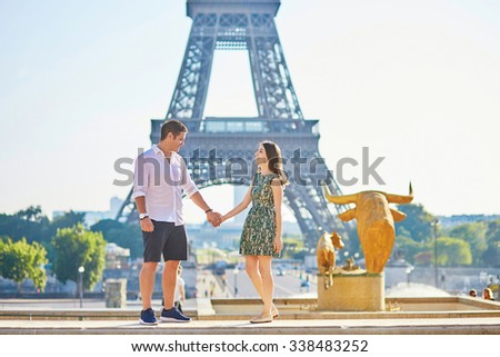 Young romantic couple in Paris near the Eiffel tower, enjoying their vacation to Paris - stock photo