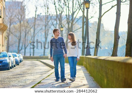 Young romantic couple in Paris, walking together near the Seine