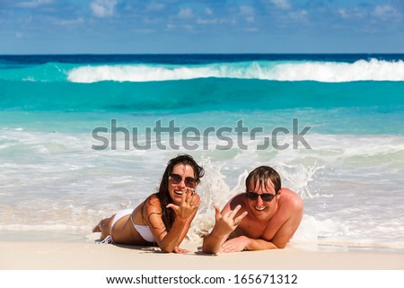 Young romantic couple laying on sandy beautiful tropical beach Seychelles La Digue - stock photo