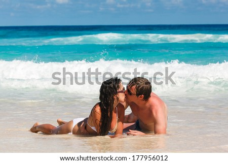 Young romantic couple laying on sandy beautiful tropical beach Seychelles La Digue