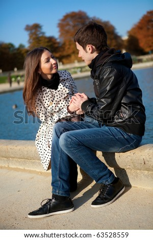 Young romantic couple near water at warm sunny autumn day - stock photo