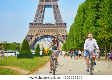 Young romantic couple of tourists using bicycles near the Eiffel tower in Paris, France - stock photo