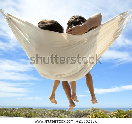 Young romantic couple relaxing in hammock on tropical beach - stock photo