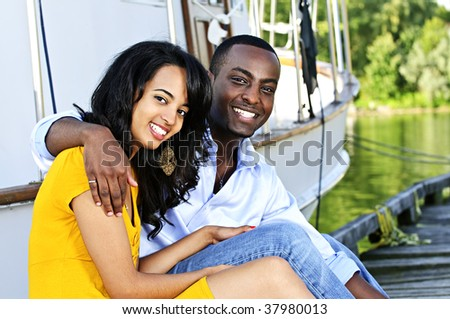 Young romantic couple sitting on dock in front of yacht - stock photo